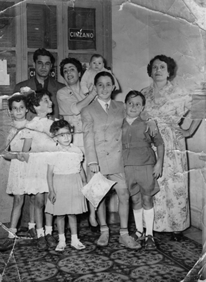 My grandmother, my father & some of his brothers, sisters, in Takett's just after his Bar Mitzvah. He is in the middle holding his Tallit.